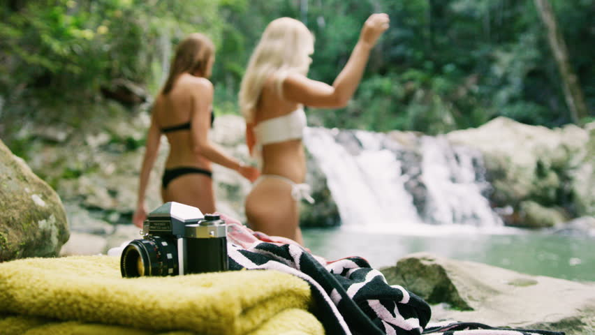 Hot girls getting ready to go swimming near waterfall. Shot with a RED camera. 4k footage.
