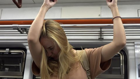 Young Caucasian Blonde Woman Sleeps Hanging on Handles While Commuting in Subway Train