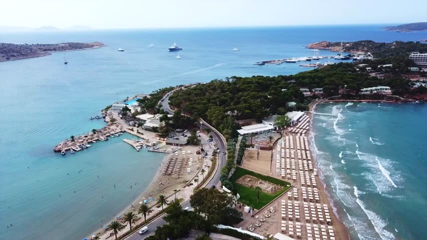 Aerial drone bird's eye video of famous celebrity sandy beach of Astir or Asteras in south Athens riviera with turquoise clear waters, Vouliagmeni, Greece