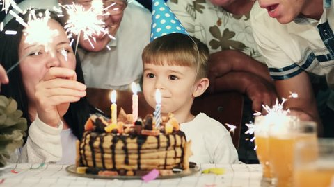 Little boy in cone hat sitting at table and blowing candles on birthday cake while his family standing behind and sing a song to him holding the Bengal lights. Boy smiling and laughing at camera