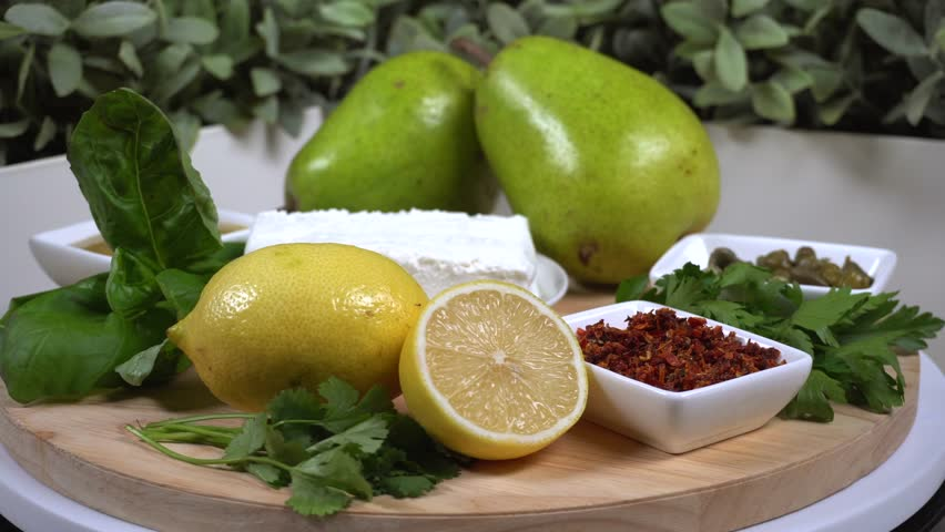 Set of products necessary to cook vegetarian meal. Close up. Cottage cheese, pear, capers, parsley, dried tomatoes, lemon, basil, mustard, onions.