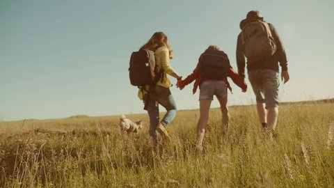 happy family slow motion video walking on nature boy girl and mom in a field on trekking trip. tourists with backpacks traveling. happy lifestyle family travel tourism concept