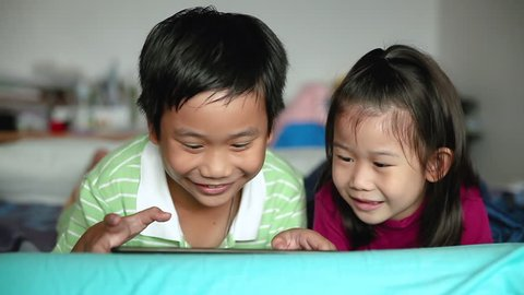 Asian children using digital tablet. Happily sister smiling and cheering her brother near by. Cute boy playing games excitedly on touchpad and lying prone on bed.
