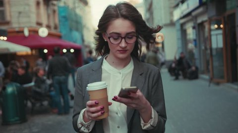 Pretty young woman with curly hair, walking cross the city center with coffee-to-go and using smartphone. Coffee break, relaxation, successful lifestyle. Female portrait