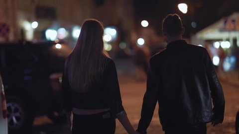 Back view of young people in love holding their hands while walking cross the night city street. Going to the party, club, concert together. Happy together, having fun. Love story