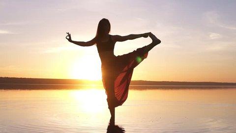 Beautiful footage on sunset beach, woman doing yoga asana Utthita Hasta Padagushthasana staying in the water. Slow motion