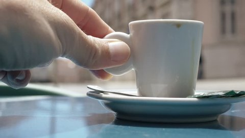 Man Drinks A Cup of Coffee In Street Bar. Male hand puts a cup of coffee on the table of a restaurant terrace after drinking it. Street life blurry background