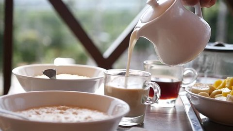 Pour the milk from the jug into the coffee at breakfast. HD, 1920x1080, slow motion