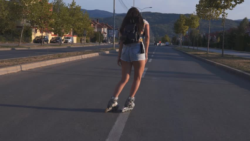 SLOW MOTION: Girl driving roller skates. Young brunette woman riding inline skates in the street downtown. | Shutterstock HD Video #1012255868