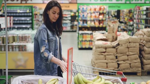 Attractive girl happy customer is choosing fruit in supermarket buying bananas, apples and oranges and putting them in shopping cart. Healthy lifestyle and shops concept.