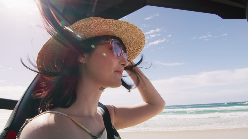 Beautiful girl wearing a hat driving dune buggy along the beach. Shot with a RED camera. 4k footage.