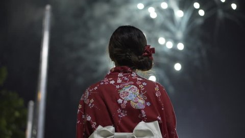 Shot from behind Asian girl in kimono waving a hand fan with fireworks in the background at a Japanese festival. Camera pans up and focus goes from girl to fireworks in 4K