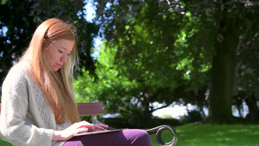 A wide shot of a young woman sitting in the park as she works on her tablet. | Shutterstock HD Video #1012304468