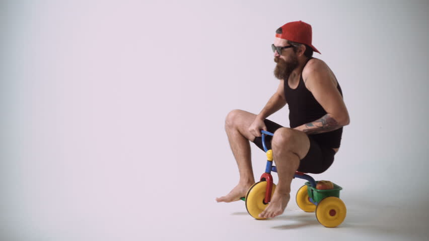 A funny bearded man is riding a children's bicycle. | Shutterstock HD Video #1012311128