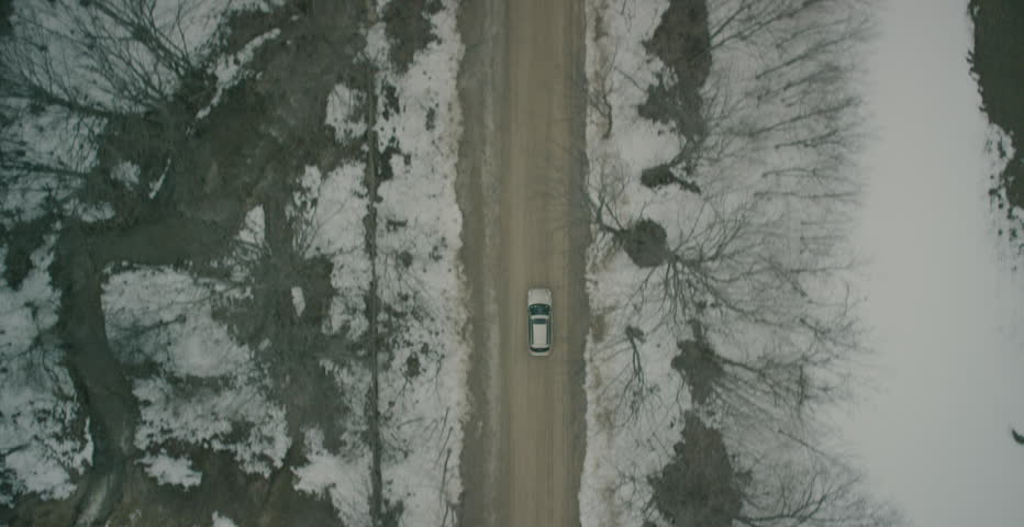 Top-down aerial of car driving through snowy landscape