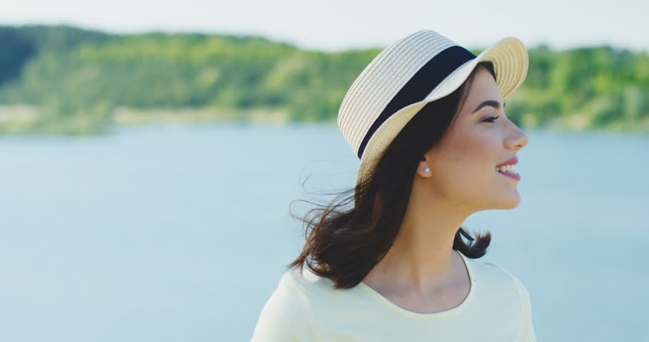 Portrait shot of the attractive Caucasian young woman in the hat smiling while turning her head to the camera on the lake background. Close up. Outdoors. | Shutterstock HD Video #1012337918