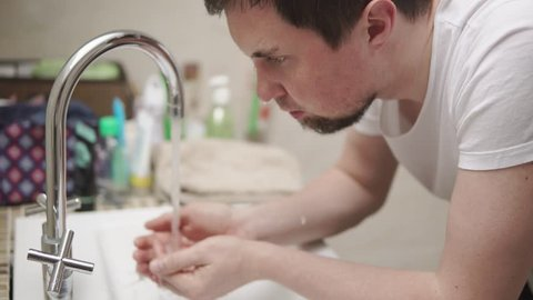 Young guy is bathing his face above a washbasin in a washroom. He is leaning down, taking water and throwing it in face after wake up