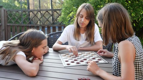 Playing checkers at terrace table teenager sisters girls triple twins have fun together