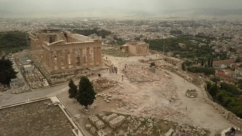 Athens Acropolis and Parthenon on cloudy day captured in 4k drone shot from above. down town surroundings.