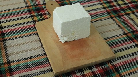 Cutting traditional bulgarian salty white cheese with a knife
