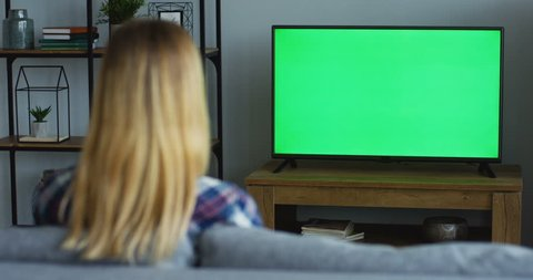 Rear of the blonde woman in the plaid blue shirt sitting on the sofa in the living room and watching TV with green screen, then changing channels with a remote control. Chroma key. Indoors