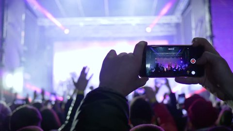 fans with mobile phones into hands delight live music at rock concert in bright scene lights in evening