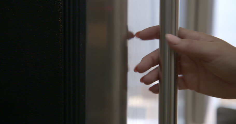 Pan across to CU on woman's hand as she opens and closes stainless steel fridge door, revealing out of focus interior with water dispenser. Real-time 4K | Shutterstock HD Video #1012397198