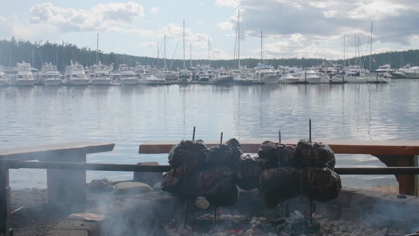 Huge Rotisserie Top Sirloin Beef Spit Roast in Fire Pit Luxury Yacht Harbor Background