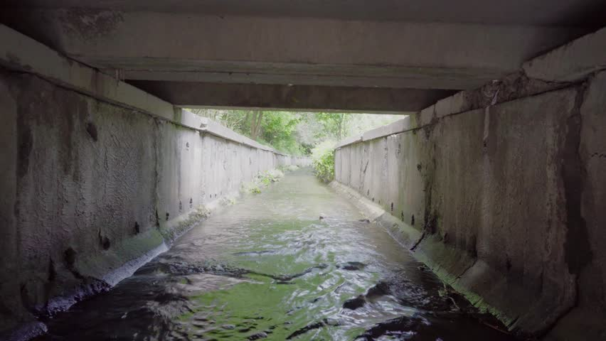 Exit from the drainage or sewage tunnel. Concrete Drainage collector of city sewage system. Wastewater flows from the pipe to the drainage canal. Drainage canals drain the fluid flow.