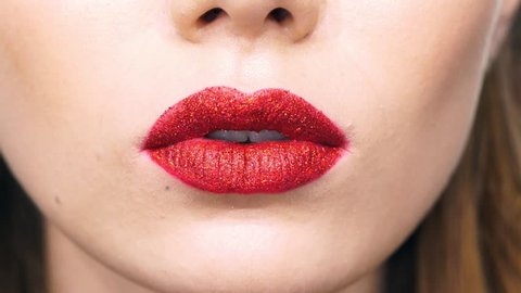 Cropped view of young smiling woman with red shiny lipstick eating yellow candy and making kiss gesture