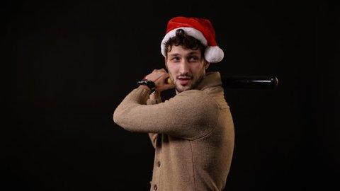 A man with a Santa hat waving a baseball bat