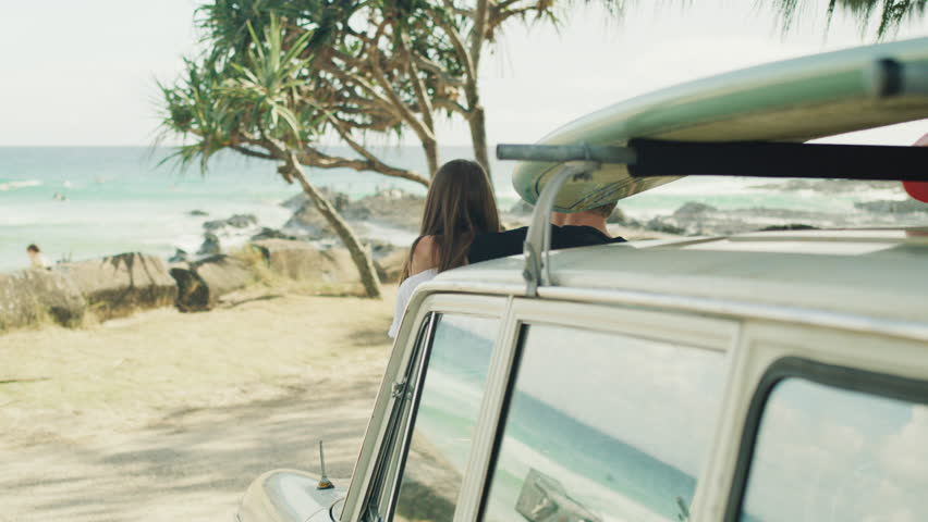 Attractive couple sitting on car and looking at the beach. Shot with a RED camera. 4k footage.