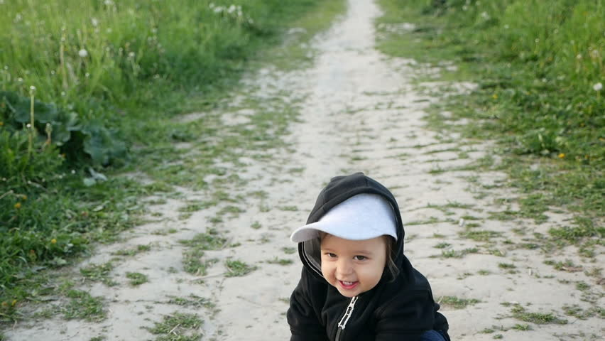 child in a jacket with a hood and a cap runs in the field along the path with playing with a ball