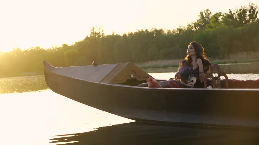 Girl sailing on a gondola down the river. Beautiful woman with carnival mask | Shutterstock HD Video #1012478768
