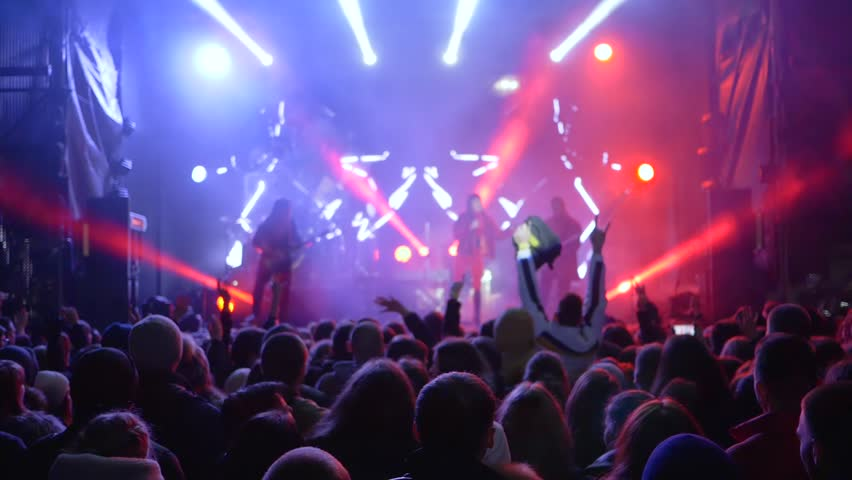 Kherson, Ukraine 30 March 2018: nightlife of youth, crowd of youth waving arms up during rock band performance on lit stage in fume in slow motion in Kherson, 30 March 2018. #1012485698
