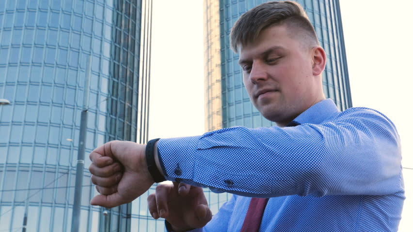 Young handsome businessman in blue shirt, looking at time, skyscraper background. | Shutterstock HD Video #1012491068