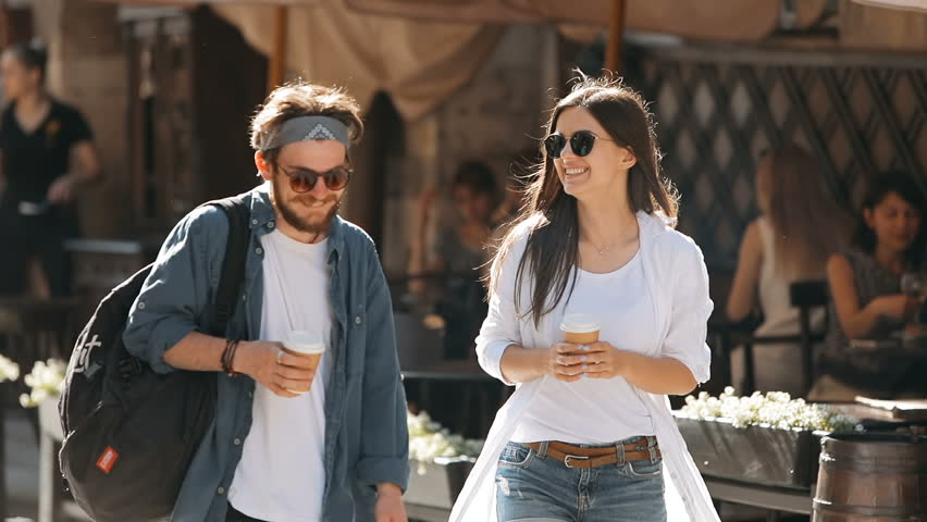 Lovely couple of students laughing as walking around the city, spending time together during summer holidays, telling funny stories and holding cups of coffee, concept of live communication among