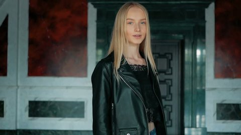 fashion portrait of a beautiful young woman with blue eyes and blonde hair in a leather jacket indoor