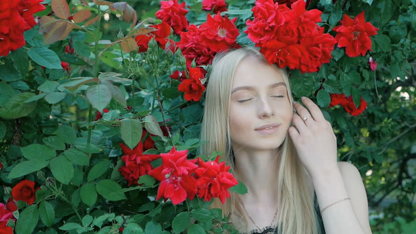 Beautiful fashionable portrait of a young woman with blue eyes and blonde hair in a outdoors in red rose garden | Shutterstock HD Video #1012515848