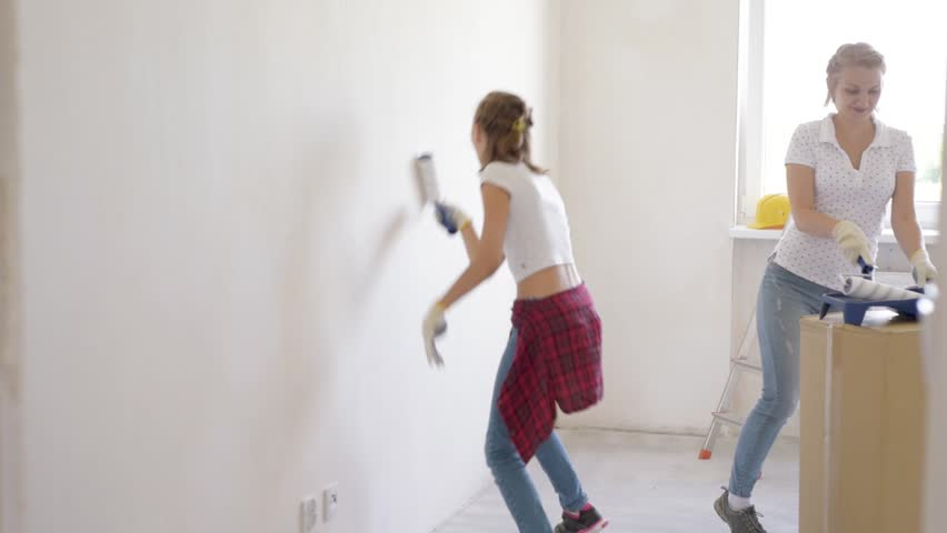 Mother and daughter painting wall in apartment room. Beautiful family doing repairs in new flat. Woman and teen girl making decorate room, laughing and having fun.  | Shutterstock HD Video #1012538228
