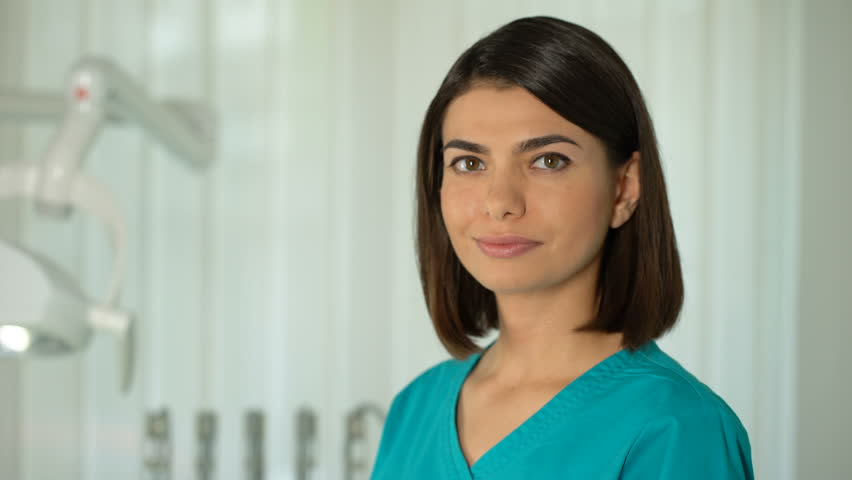 Charming female doctor posing for camera, confidence and professionalism, clinic | Shutterstock HD Video #1012572968