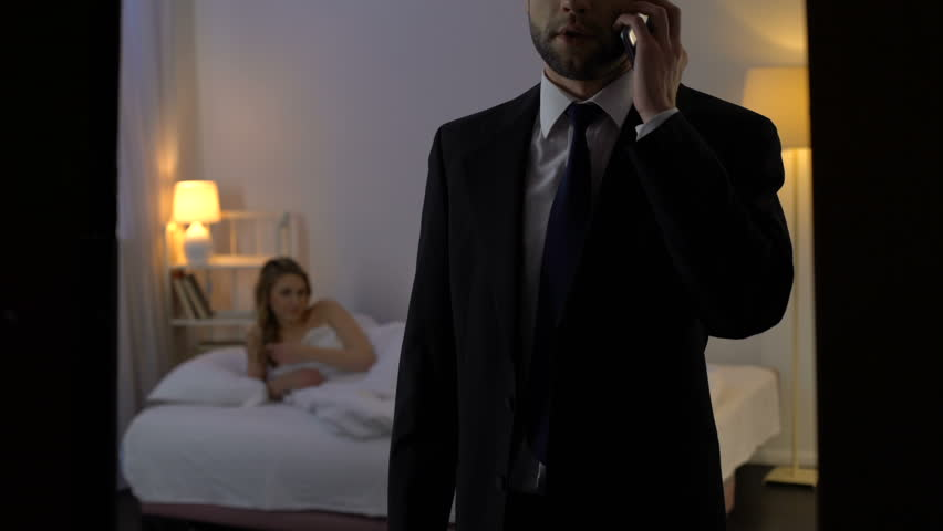 Man talking on phone, lying to wife while spending time with mistress in hotel