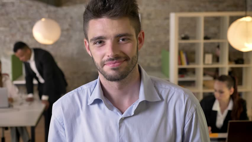 Young businessman is watching at camera in office, smiling, his colleagues are networking with technologies, working concept, business concept, communication concept, blurred background | Shutterstock HD Video #1012600598