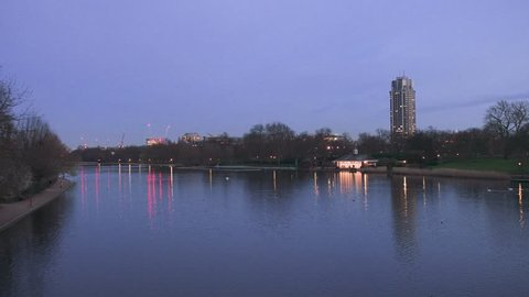Dusk scene of The Serpentine lake in the Hyde Park with a view to the Hyde Park Barracks military base and London architecture buildings