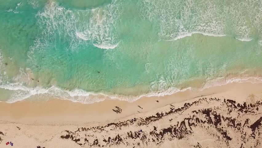Aerial view looking straight down on a semi-crowded beach as waves crash on the east coast of Cozumel Mexico. Flying right to left.