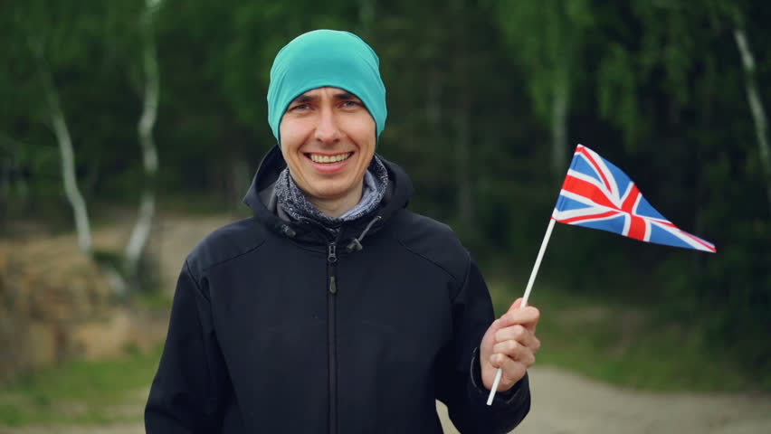 Slow motion portrait of smiling Englishman sports fan holding UK flag flying in the wind and looking at camera. Nationalism, sport and people concept. | Shutterstock HD Video #1012648898