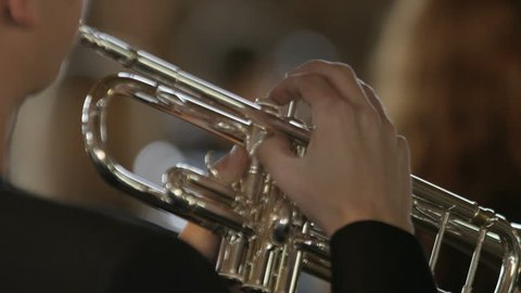 Close up of a boys hands playing trumpet, camera focuses onto girl with clarinet