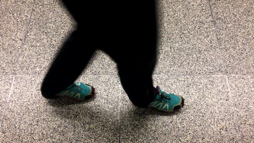 Person walking by on mosaic flooring wearing blue sports shoes | Shutterstock HD Video #1012671158