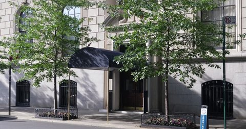 A daytime exterior establishing shot of a typical Manhattan upscale apartment building's entrance with awning over sidewalk.