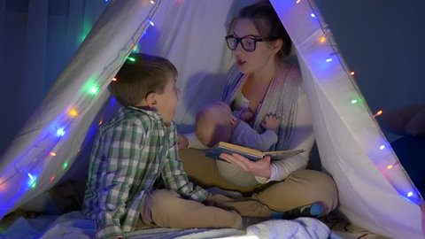 family leisure, mother reads an interesting book to her two sons sitting in the wigwam in the evening